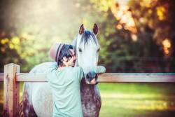 Jungen Mann umarmt ein Pferd