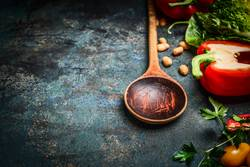 Alter Löffel und frisches Gemüse für Vegan Kochen.