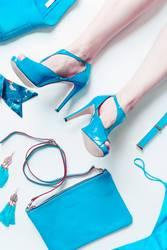 Frauenbeine mi High Heels und türkis Accessoires