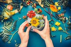 Weibliche Hände machen Herbst Blumen Deko