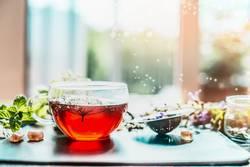 Tasse mit Kräutertee am Fenster
