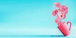 Rosa Tasse mit fliegende Blumen. Sommer concept