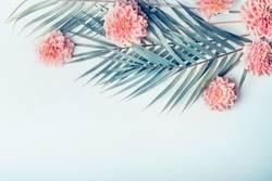 Palmenblätter und tropische Blumen