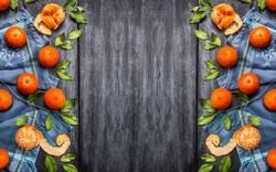 Frische Mandarinen mit Blättern auf blauem Hintergrund
