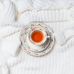 Tasse Tee auf gestrickter Strickjacke