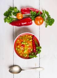 Minestrone Suppe auf weißem Holztisch mit Gemüse und Löffel