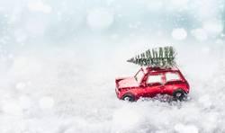 Rotes Auto fährt Weihnachtsbaum in Schnee