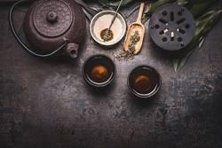 Asiatischer grüne Tee mit Teekanne, Schalen, Kerze