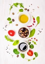 Salat Vorbereitung mit Dressings, Oliven, Wildkäuter,Chili, Öl