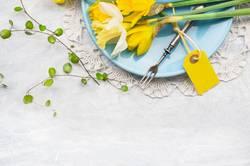 Teller mit Frühlingsblumen, Gabel und Karte