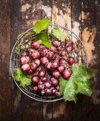 Rose Weintrauben mit grünen Blättern
