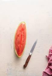 Stück Wassermelone auf weißem Tisch mit Messer