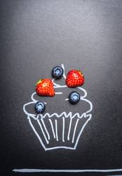 Frische Beeren auf gemaltem Kuchen auf Tafel Hintergrund