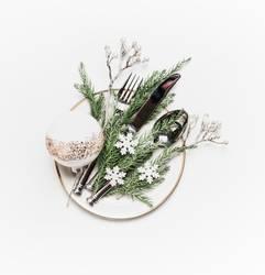 Teller mit Besteck und Weihnachtsdekoration auf weiß