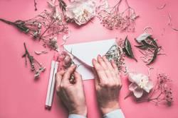 Hände dekorieren Briefumschkag mit Blumen