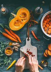 Weibliche Hände schneiden Gemüse für Kürbissuppe
