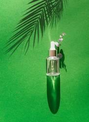 Flasche mit Pipette auf grünem Tisch