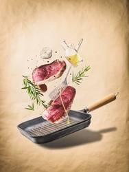 Fliegen rohe Steaks, mit Kräutern, Öl , Gewürze und Pfanne