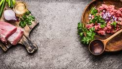 Fleisch auf Schneidebrett mit Hackfleisch, Löffel und Zutaten