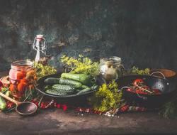 Gurken und Tomaten in Gläser einlegen