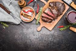 Geschnittenes Grill Steak auf Schneidebrett mit Wein und Gewürze
