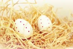 Rot gepunktete, weiße Eier im Stroh