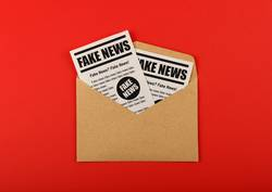 Envelope with FAKE NEWS newspapers over red