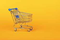 Close up retail shopping cart over yellow