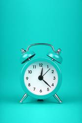 Close up one teal blue alarm clock over turquoise