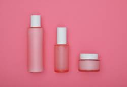 Set of beauty cream bottles over pink background