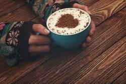 Frauenhände, die großes Cup Cappuccinokaffee umarmen
