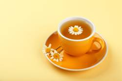 Yellow cup of herbal tea with camomile