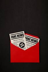 Envelope with FAKE NEWS newspapers over black
