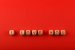 Wooden cubes with I LOVE YOU words over red