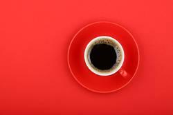 Schwarzer Kaffee in der roten Schale mit Untertasse auf rotem Papier, Draufsicht