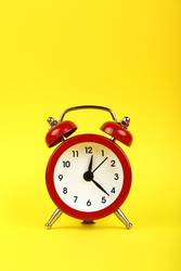 Close up one red alarm clock over yellow background