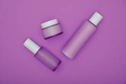 Set of beauty cream bottles over purple background