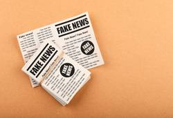 Stack of FAKE NEWS newspapers over brown paper