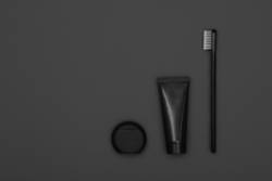 Black toothpaste and toothbrush over grey