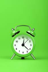 Close up one alarm clock over green background