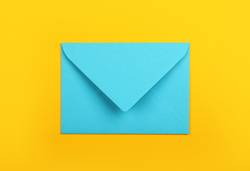 Closed blue paper envelope over yellow