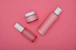 Set of cosmetic skin care cream bottles on pink