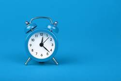 Close up one blue alarm clock over blue background