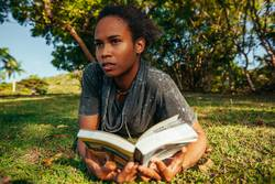 Young afro american woman reading book lying on the green lawn