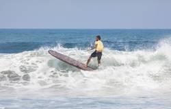 Surfer on longboard performing maneuver in white breaking wave