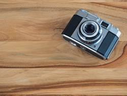 analoge Kleinbildkamera auf braunem Holztisch
