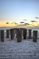 Dilapidated ruins of a pier on Port Royal Beach at sunset
