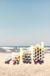 Stacks of plastic straws on a beach.