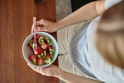 Pregnant woman eating a bowl of fruit salad