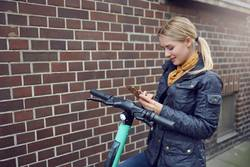 Trendy young blond woman booking e-scooter